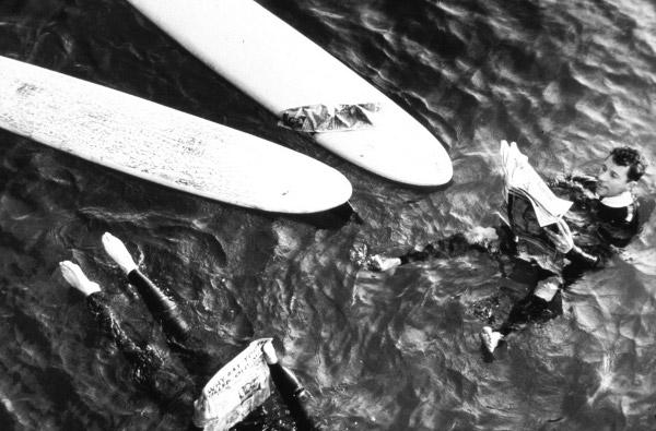 60-те години. Водолаз с костюм O'Neill демонстрира ползите от неопреновия костюм, четейки вестник във водата.