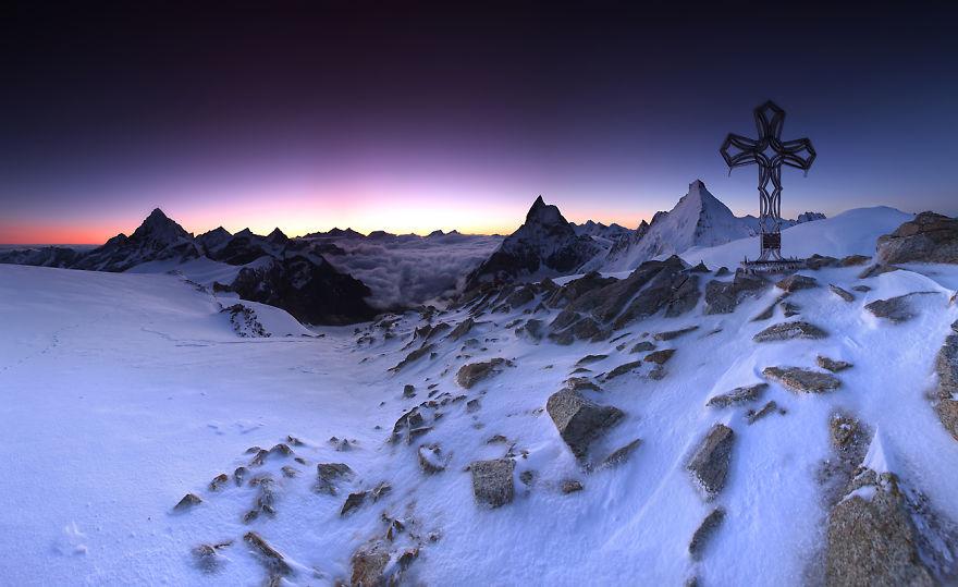 Кръст, извисяващ се над замръзналите Алпи